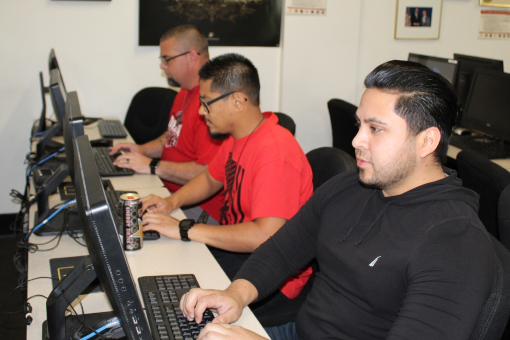 Veterans Dante Tapia Garcia (front), Arthur Matedne (center), and  Jeremy Caylor research GI Bill benefits at Delta College.