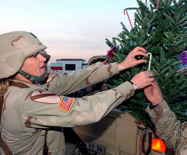 Army Pfc. Erika Bruner, of Headquarters Company, 4th Brigade Combat Team, 1st Cavalry Division, places the traditional topper on a real, Douglas fir Christmas tree. Photo by Cpl. Benjamin Cossel, USA