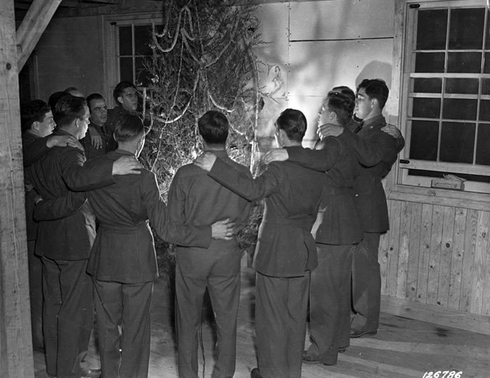 CHRISTMAS - ARMY STYLE 1941. All Pennsylvania soldiers in Co. B of the 10th Regiment in Camp Lee's Quartermaster Replacement Center gather to sing carols around the tree to show how men of the Keystone State demonstrate Christmas spirit. Camp Lee, Virginia. December 1941.