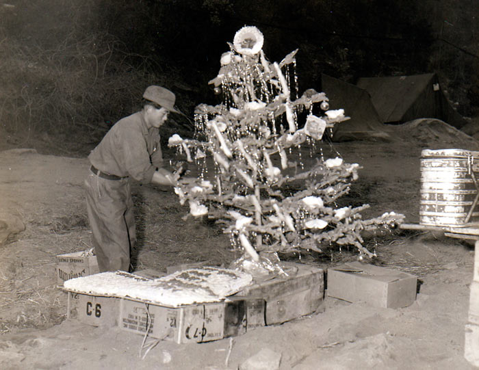 Korean KP decorates Christmas tree set up in front of serving counter of HQs & HQs Co, 19th Inf Regt, 24th US Inf Div, as Christmas Day dinner is readied for men of the Co. Korea. 25 December 1951.
