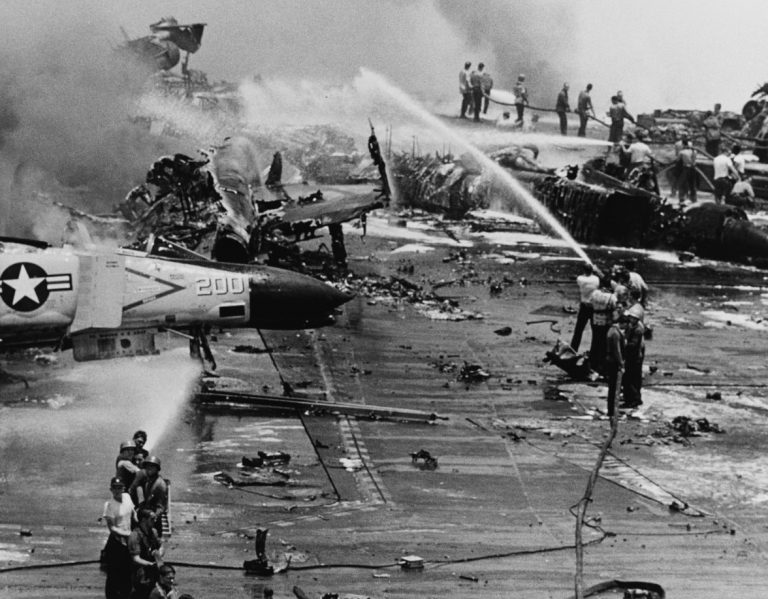 The deck and aircraft are on fire during the July 1967 disaster.