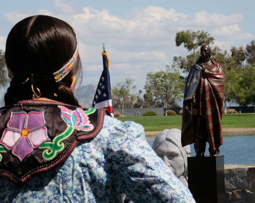 Photo taken during groundbreaking ceremonies in 2017, Native American looking at the area where the Gift would stand.