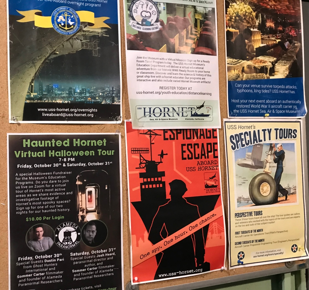 A picture of event flyers hanging on the entrance door to the USS Hornet.