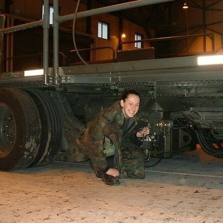 Christy in work fatigues working on large diesel machine. Dover Air Force Base.