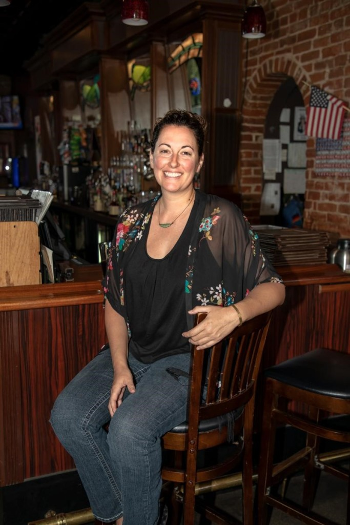 Photo of a smiling Christy, proudly sitting on a barstool in her restaurant.