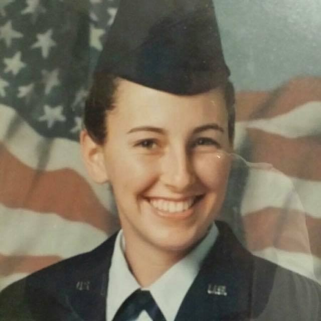 Photo of a smiling young Christy in service uniform, in front of American flag. U.S. Air Force. Morro Bay High Grad.