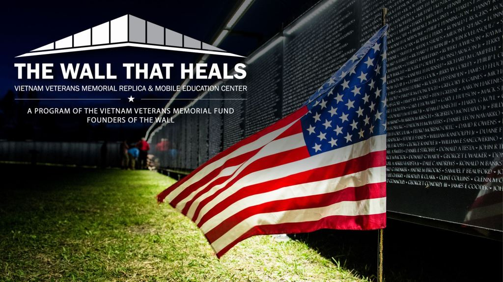 Photo of the mobile replica of the Vietnam Veterans War Memorial with text that reads: The Wall That Heals. An American flag flies in the foreground.