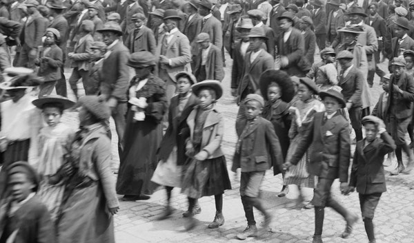 Black and white photo of African Americans parading down a street celebrating Juneteenth.