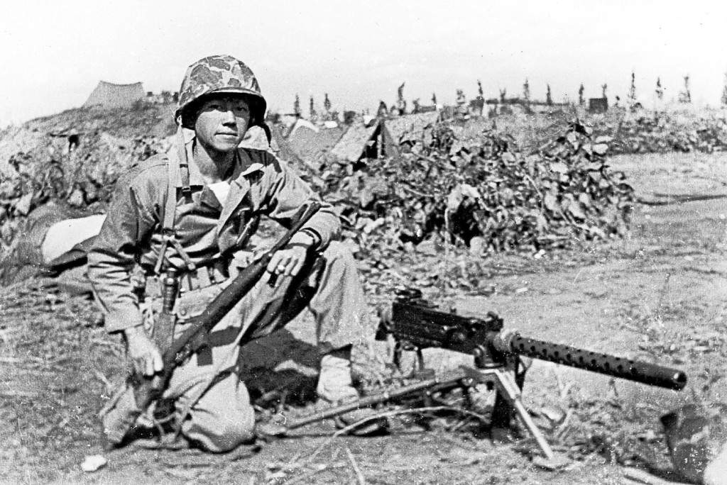 Lee in combat fatigues beside a machine gun in Korea.