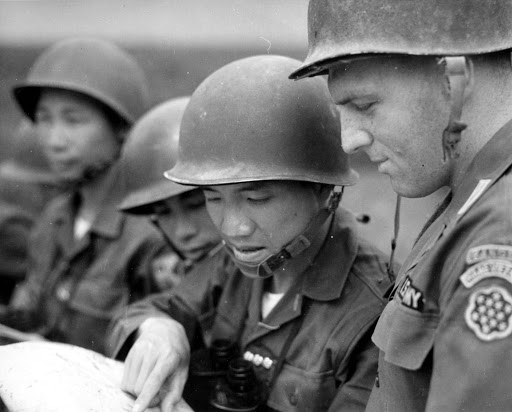 U.S. military and south Vietnamese consulting a map.
