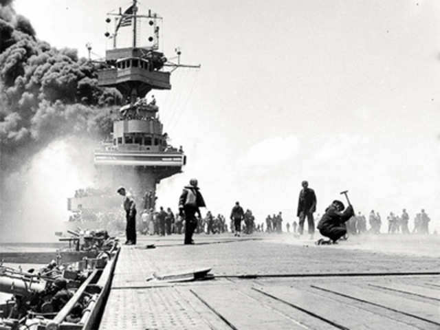 Yorktown has been hit by enemy fire and the deck billows smoke.