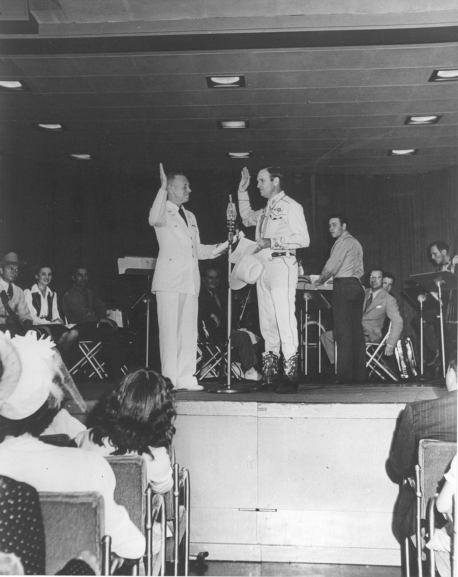 Gene Autry raises right hand as he takes oath to enlist in the military.