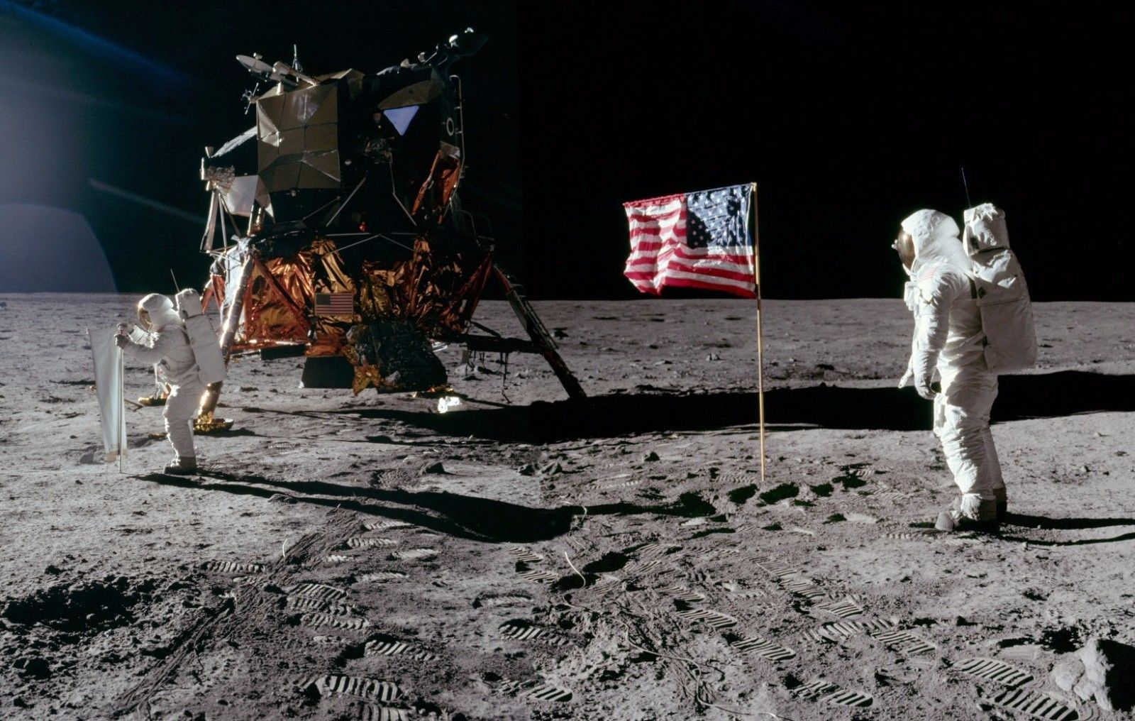 Astronauts photographed with U.S. flag and lunar command module on moon's surface.