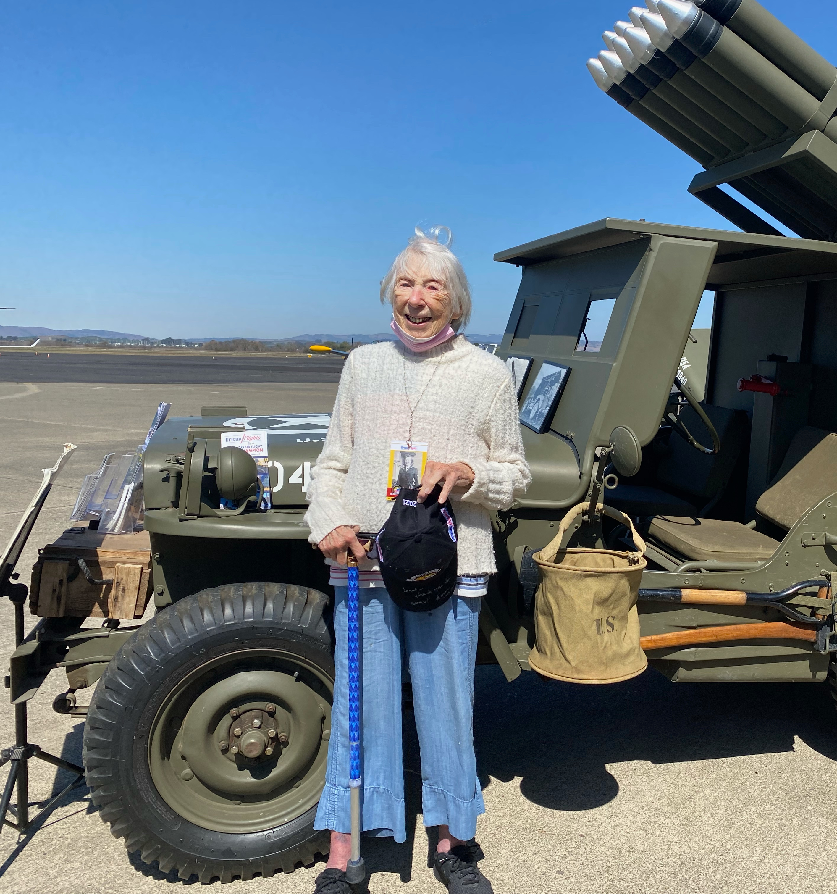 US Navy WAVE Janet Mull stands next to an old Army Jeep.
