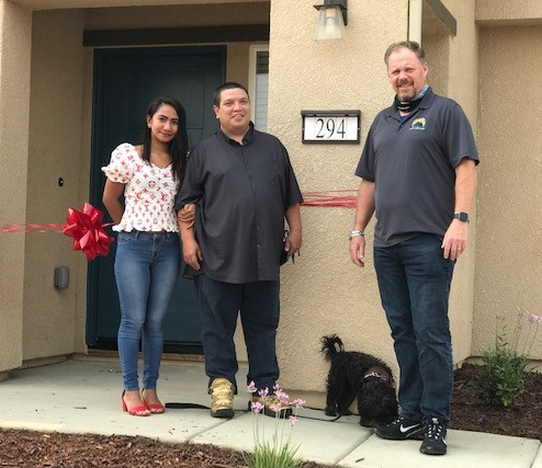 Photo of front door of new home with new owners and the man who helped them get the loan.