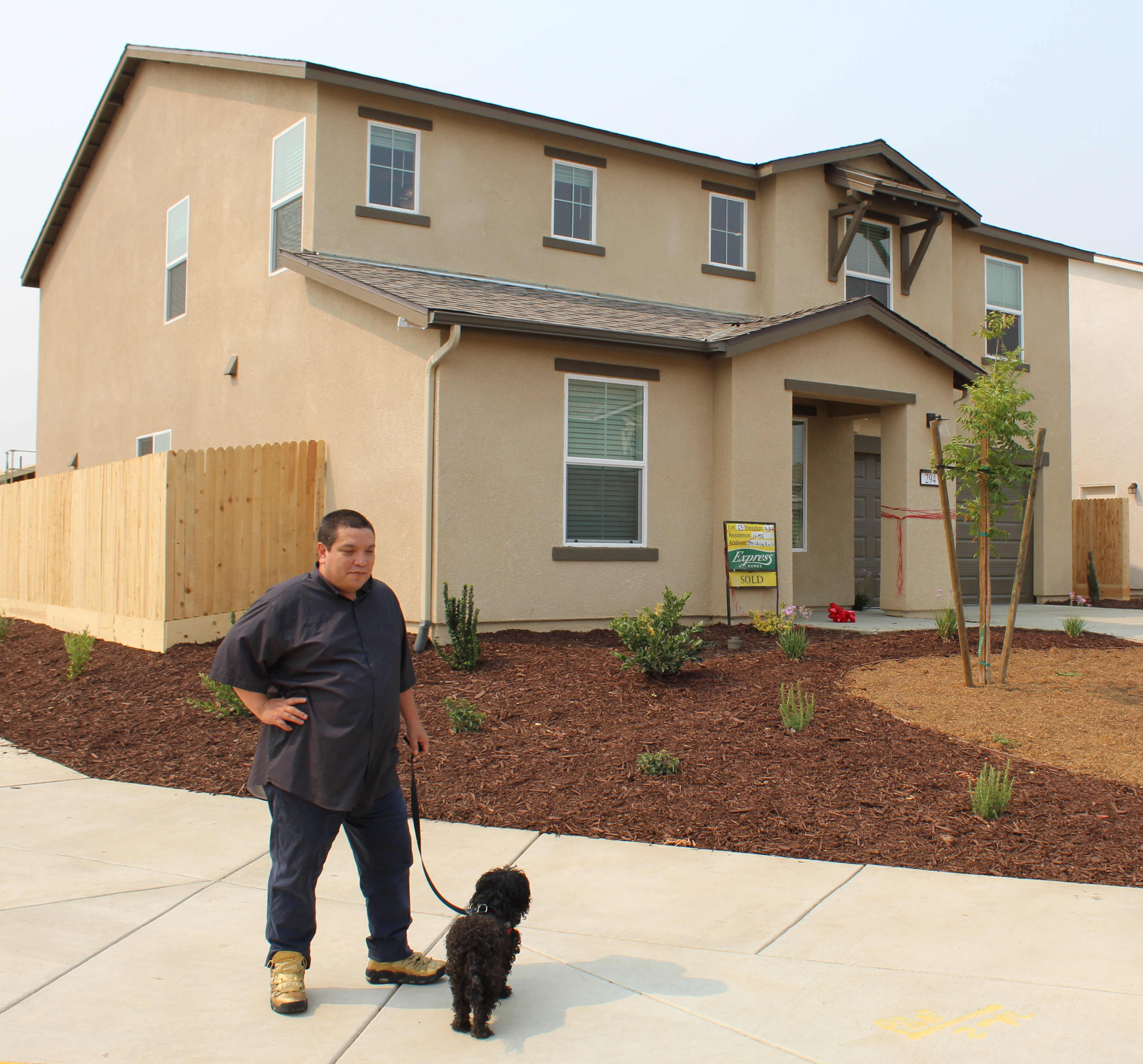 Photo of Veteran taking possession of two story beige home that sits on a corner lot in Merced.