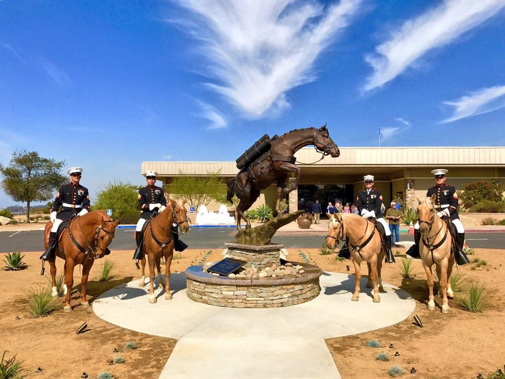 Monument to Sgt Reckless surrounded by four mounted Marines