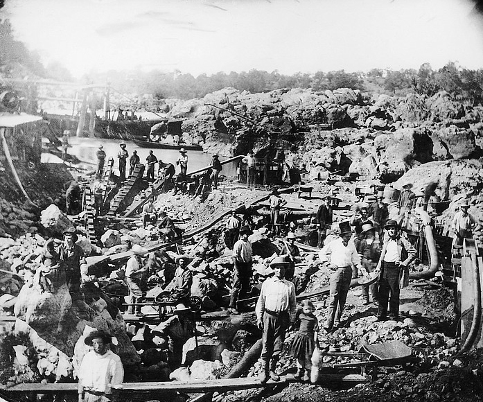 A photograph of diggings at the American River during the Gold Rush, Men, women and children are standing near a body of water with their tools.