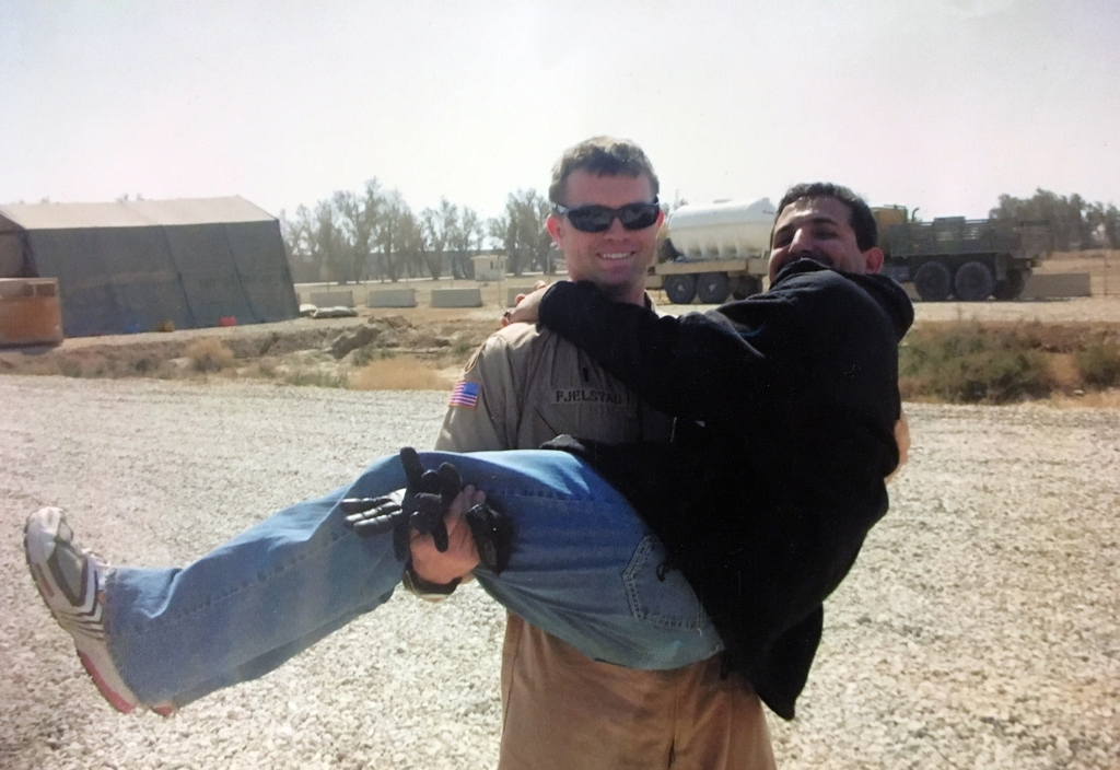 An American solder, Josh Fjelstad carries interpreter Khaleel Yasir in his arms.